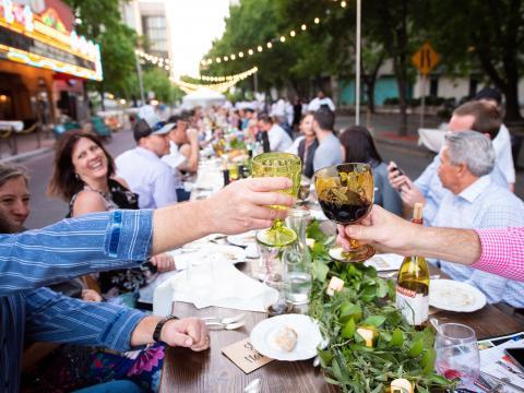 Dîner sur la rue principale de Stockton à une longue table en plein air pendant le festival Feast at the Fox qui met à l'honneur une restauration de la ferme à l'assiette
