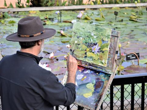 An artist painting the water lilies at Civic League Park during the EnPleinAirTEXAS National Competition & Cinch Roping Fiesta in Texas